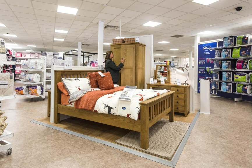 Matalan store bed display with woman in background