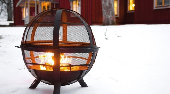 Landmann Ball Of Fire Fire Pit In The Snow With Chalet Behind It