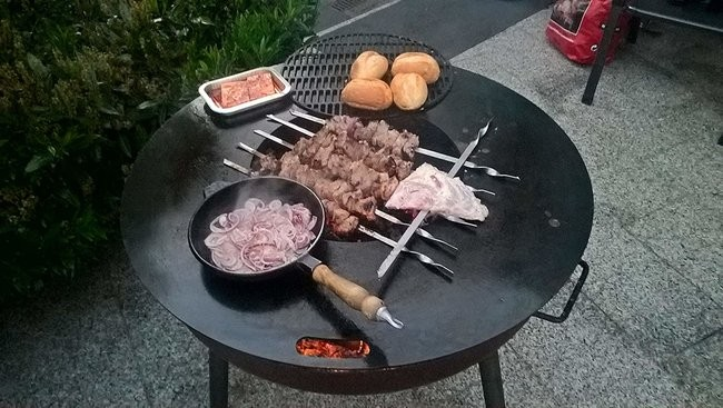 Meats and vegetables barbecuing in a fire bowl in the garden