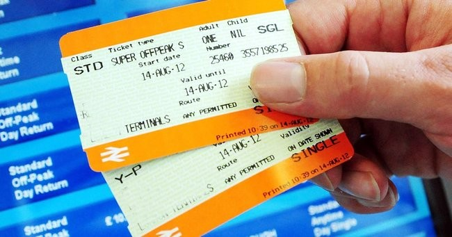 Hand holding train tickets with a ticket machine screen in the background